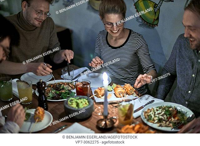 best friends enjoying dinner in restaurant Blitz, Museumsinsel, near Isartor, Munich, Germany. South-African and vegetarian food.. German ethnicity