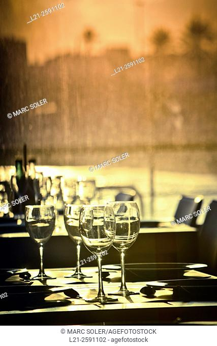 Cups, plates and cutlery on a table. Through the window there is a blurred landscape at sunset