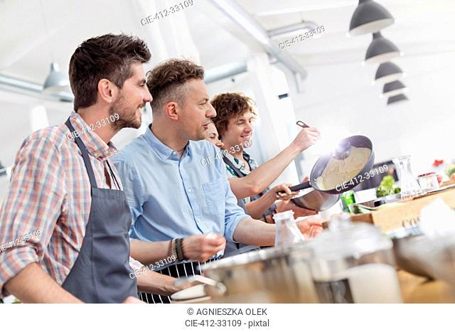 Male students enjoying cooking class in kitchen