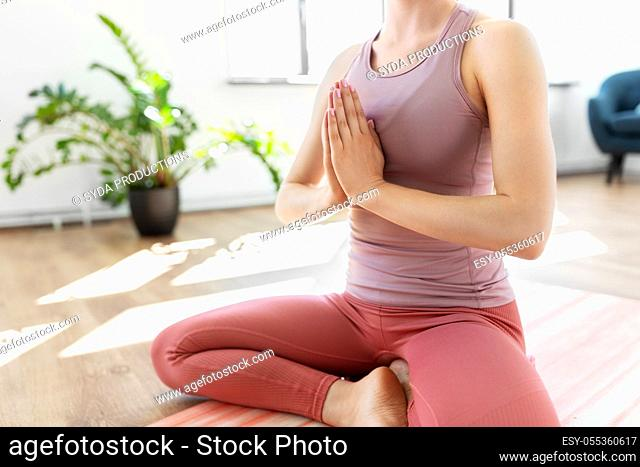 close up of woman meditating in lotus pose at home