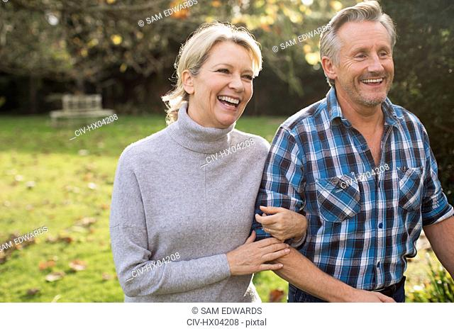 Happy, carefree mature couple walking arm in arm in sunny autumn park