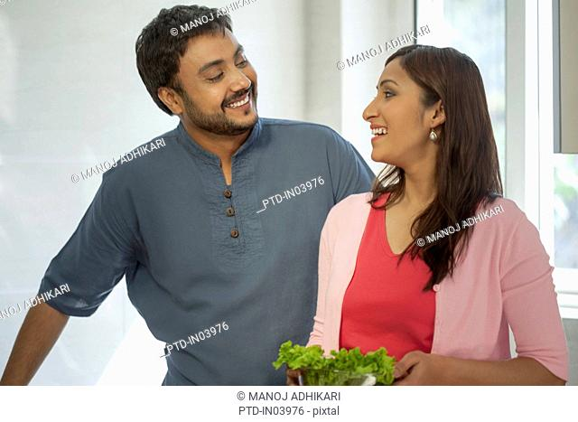 India, Man and woman standing in kitchen holding salad bowl