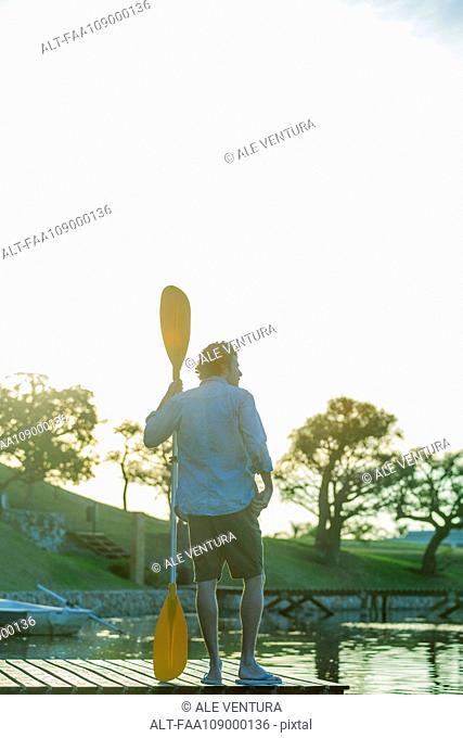 Man standing on dock with oar in hand