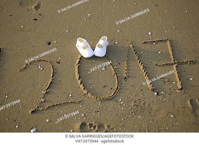 Year of birth and the shoes of his future daughter in the sand of the beach of Cullera, Valencia, Spain