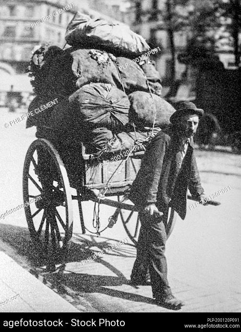 19th century photo of rag-and-bone man / ragpicker pulling hand cart / handcart loaded with unwanted rags, metal and other household waste in city