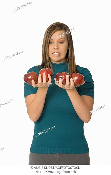Attractive woman in her 20s comparing apples to apples