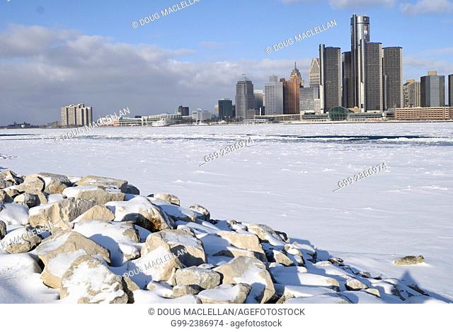 Rocky shoreline near the iced covered Detroit River with Detroit in the background view from Windsor, Ontario, Canada