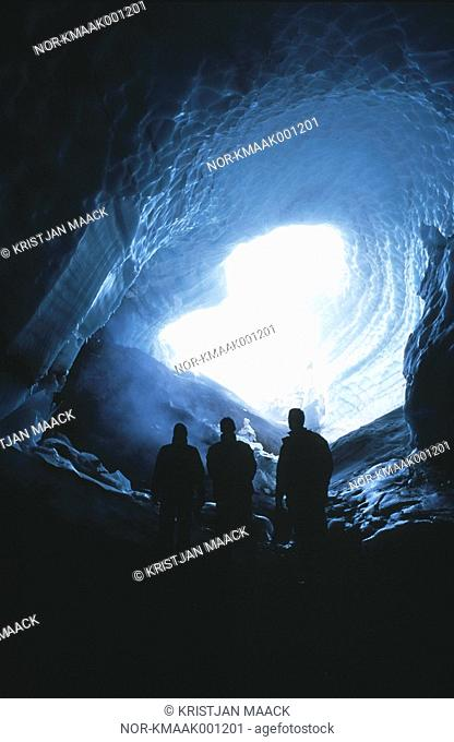 Three people inside a cave with daylight behind them, Iceland