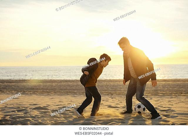 Father and son playing football on the beach at sunset