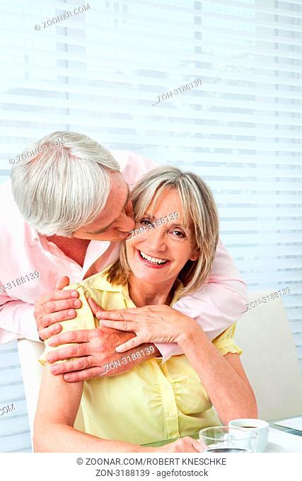 Senior küsst seine lachende Frau am Frühstückstisch