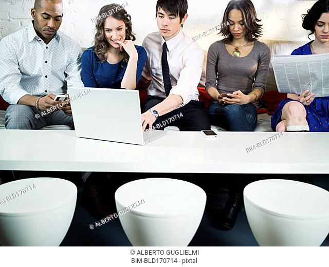 Business people using laptop in office lounge