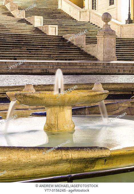 The Fontana della Barcaccia (Fountain of the Ugly Boat) on Piazza di Spagna with Spanish Steps (Scalinata di Trinità dei Monti) . Rome, Italy