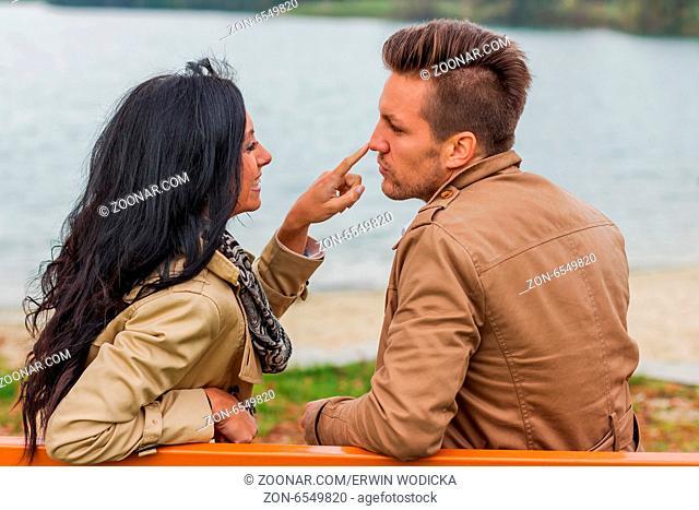 Ein junges, verlliebtes Paar sitzt auf einer Parkbank
