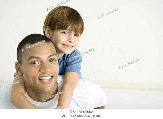 Boy leaning over father's shoulders, both smiling, portrait