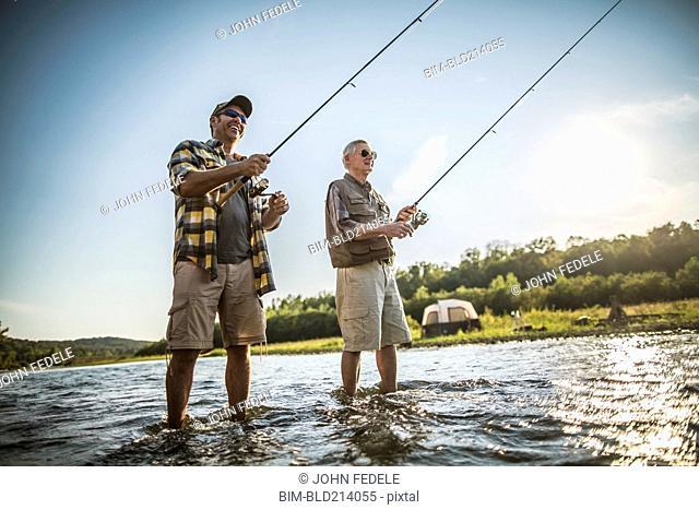 Caucasian father and son fishing in river