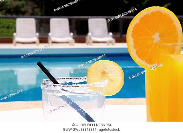 Lounge chairs with juices on table at the poolside