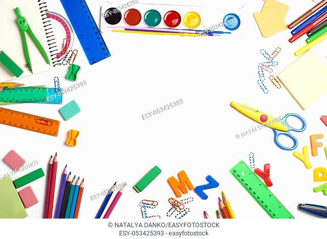 school supplies: multicolored wooden pencils, paper stickers, paper clips, pencil sharpener, copy space