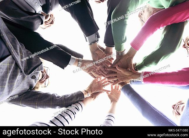 Group of friends putting hands together, directly below image