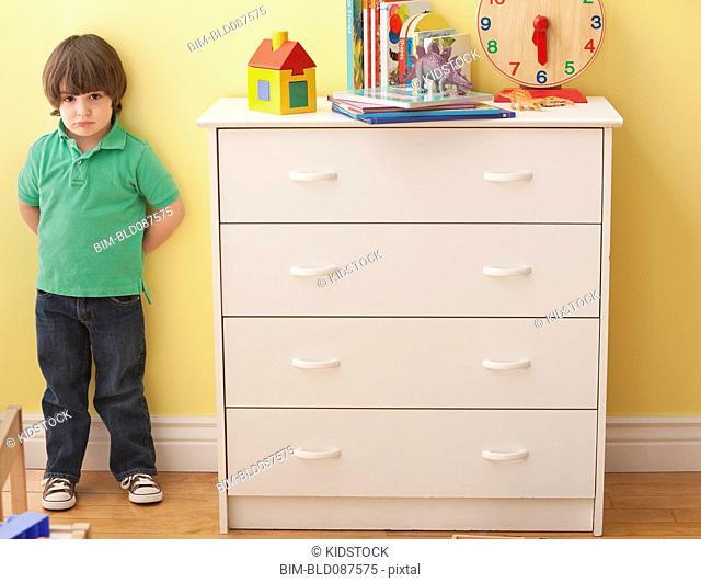 Sad Caucasian boy standing in bedroom