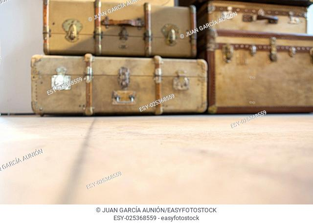 Antique brown leather luggage suitcases on the floor. Totally out of focus