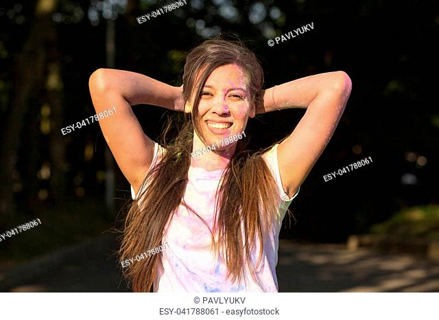 Adorable young asian woman having fun with Holi paint exploding around her