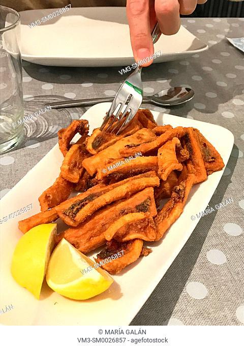 Eating rabas, fried squid. Cantabria, Spain