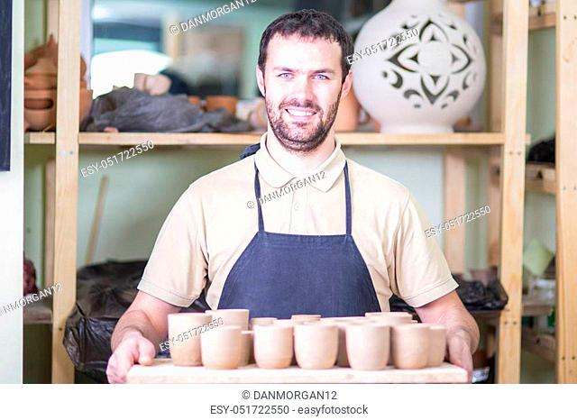 Happy Smiling Professional Male Ceramist Holding Wooden Tray with Clay Handmade Cups. Posing in Protective Apron in Workshop. Horizontal Composition