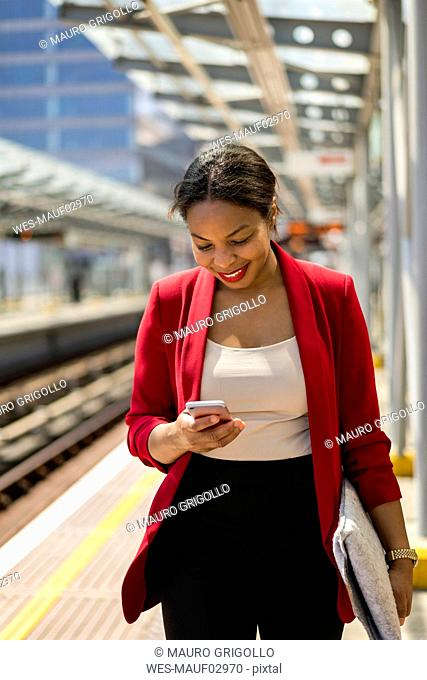 Smiling businesswoman on platform looking at mobile phone, London, UK