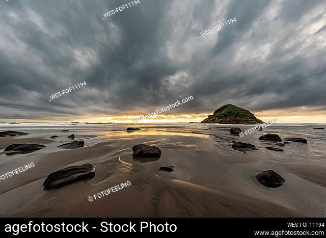 New Zealand, Tongaporutu, Cloudy sky over sandy coastal beach at dusk with Motuotamatea island in background