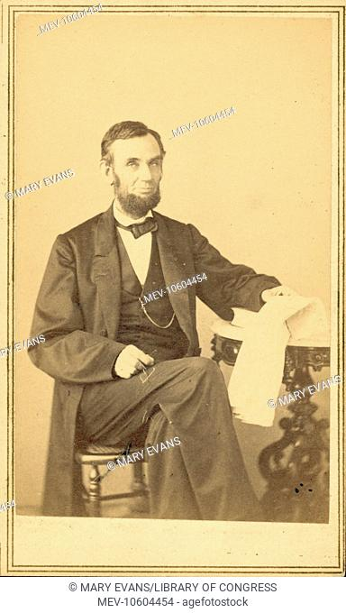 Abraham Lincoln, US President. Seated portrait, holding glasses and newspaper, Aug. 9, 1863. Lincoln poses in Gardner's new gallery on Sunday, August 9, 1863