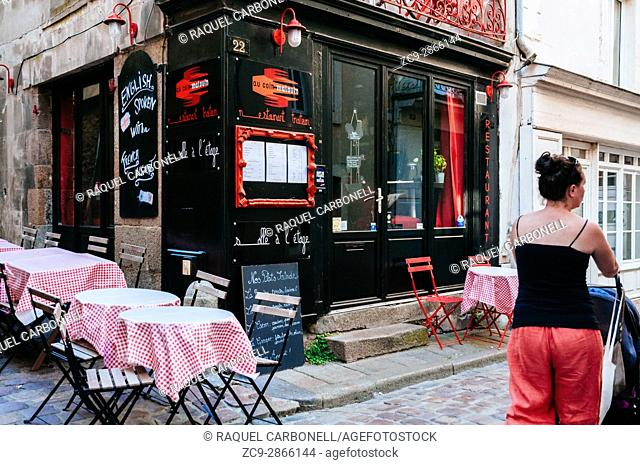 Woman walking down street passing by tipical restaurant terrace. Saint Malo, Brittany, France