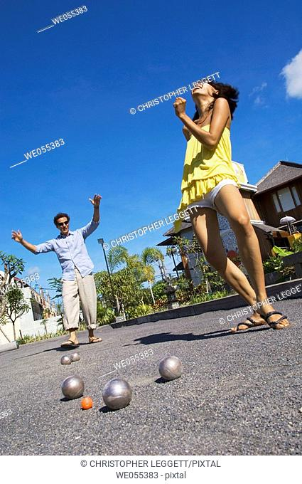 couple playing bocce and dancing