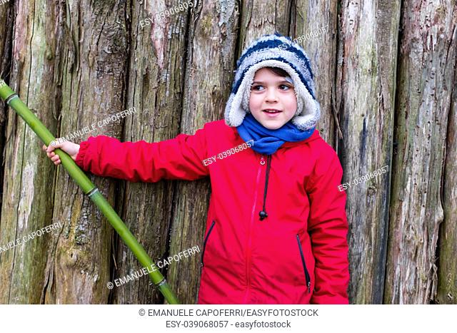 portrait of smiling 10 year old boy dressed in red jacket, leaning on a bamboo, with wooden planks background
