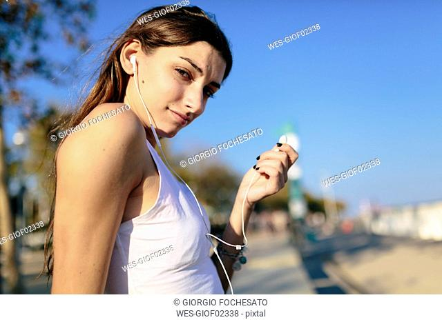 Young woman relaxing on beach promenade at sunset listening music with earphones