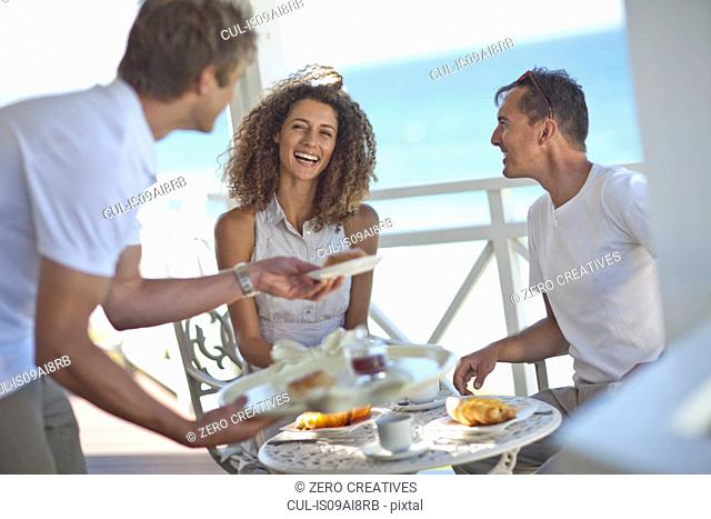 Couple having breakfast on beach house balcony