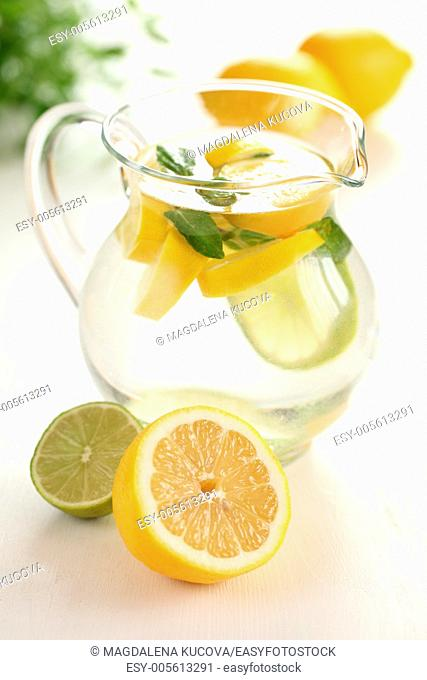Jug of fresh lemon lemonade with mint leaves
