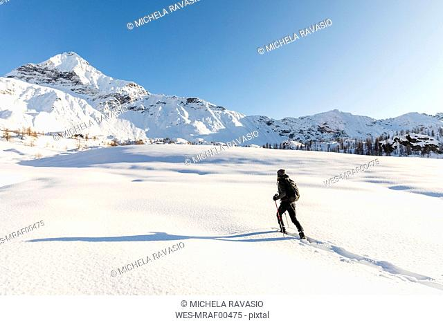 Woman walking with snowshoes in fresh snow in the mountains, Valmalenco, Italy
