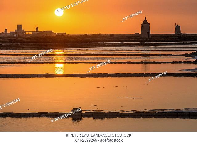 Sunset across the saltpans and windmills at the wildlife Reserve near Nubia, south of Trapani, on the west coast of Sicily, Italy