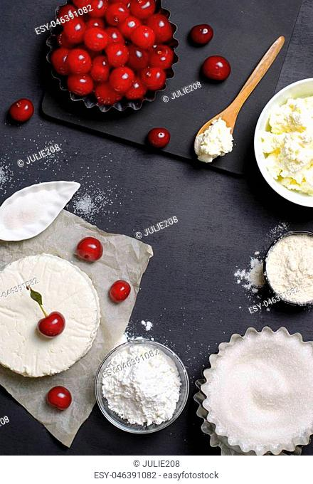 Dairy Products, Flour, Sugar and Cherries on Black Background, copy space