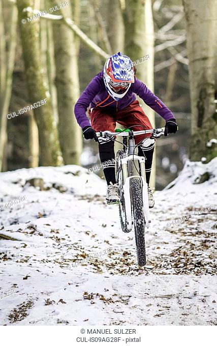 Young female mountain biking in winter forest
