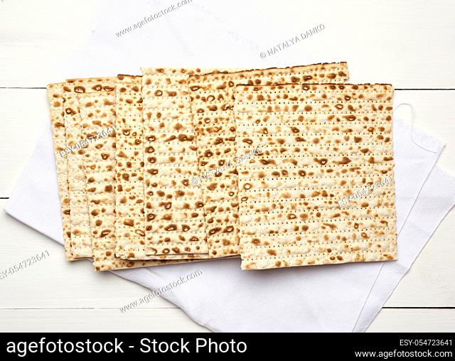 stack of baked square matzo on a white wooden background, top view