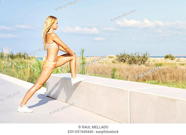 attractive female athlete stretching legs and exercising, sporty woman doing warm up workout at promenade before training and running