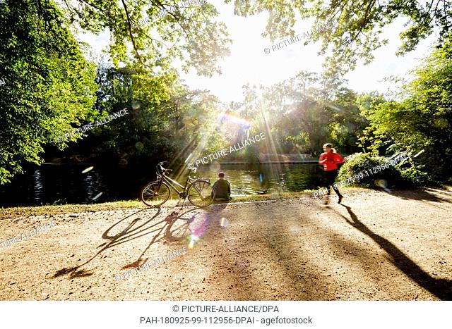 25 September 2018, Berlin: A woman sits next to her bicycle at the Landwehrkanal in the Tiergarten in the evening sun, while a jogger passes by