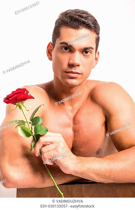 Young muscular man with perfect torso is holding single rose while standing against white background