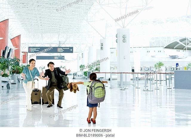 Asian grandparents greeting granddaughter in airport
