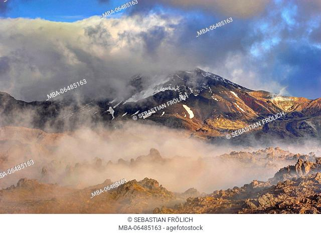 Morning fog and light mood in the Oturere Valley, Tongariro national park, New Zealand. Clouds drag about cleft volcanic rock, with different grass