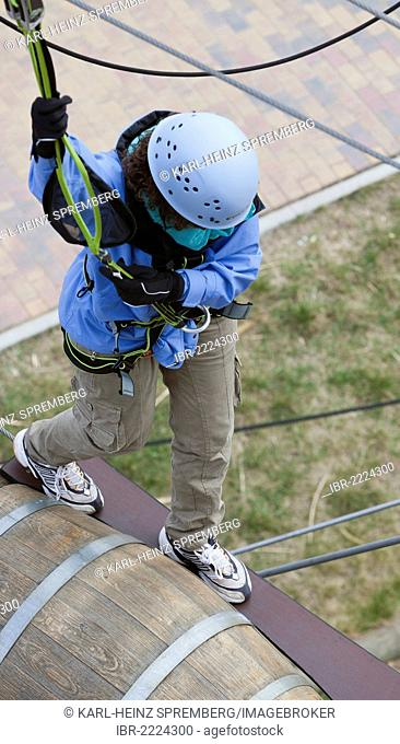Woman climbing in a high rope course, Berlin, Germany, Europe