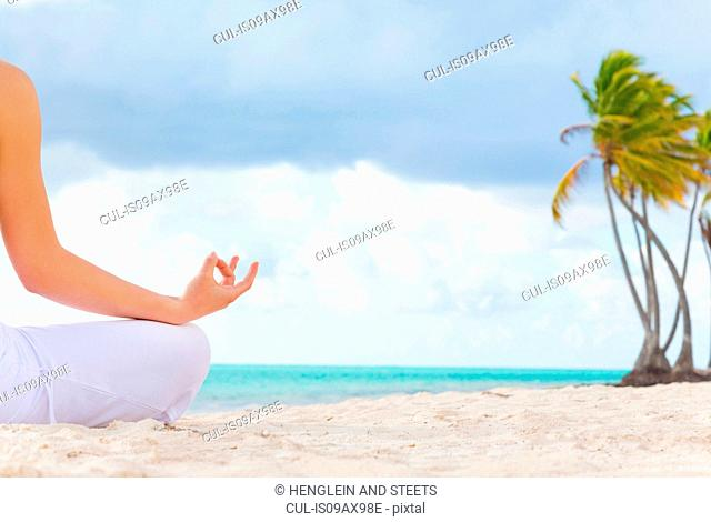Cropped rear view of young woman practicing yoga lotus pose on beach, Dominican Republic, The Caribbean