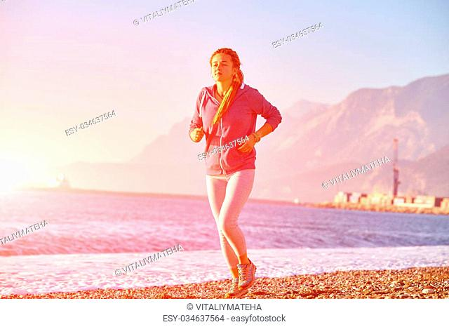 young woman running on the beach against sea and blue sky at early morning