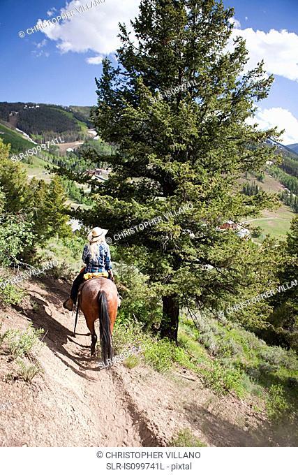 Woman horse riding through Beaver Creek, Colorado, USA